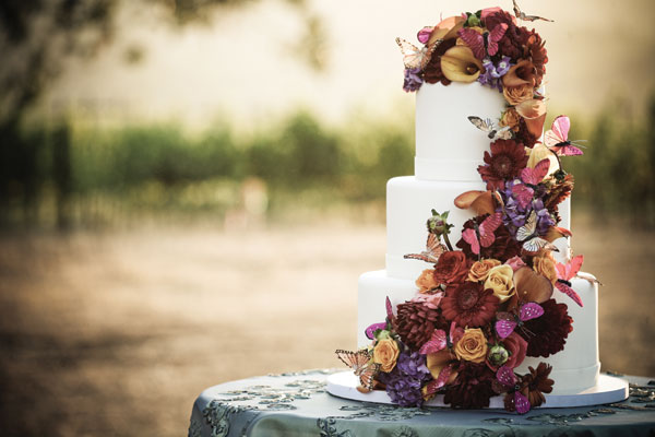 Stunning fall wedding cake featuring a cascade of autumnul orange and purple flowers, and purple butterflies
