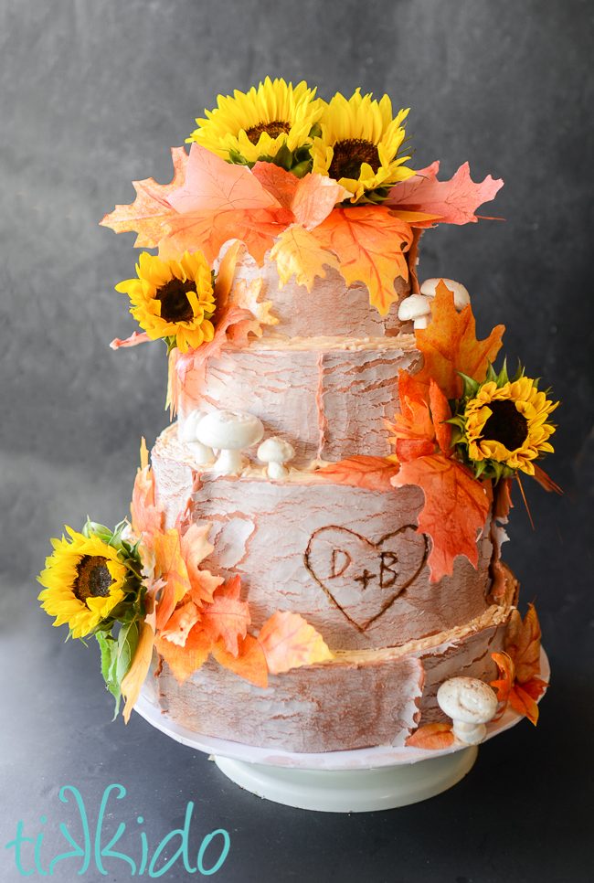 fall wedding cake with bark effect fondant, sunflowers, and edible leaves