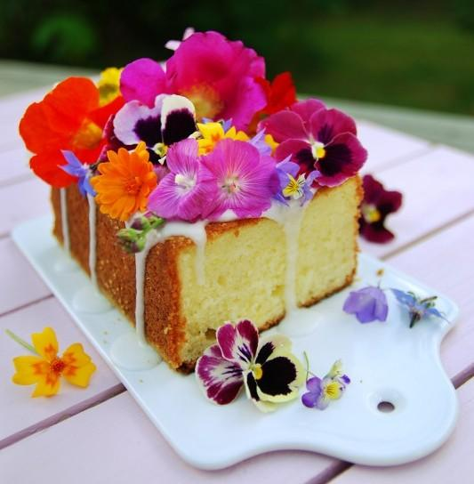 lemon cake topped with colorful pink purple and orange edible flowers, on a white cutting board.