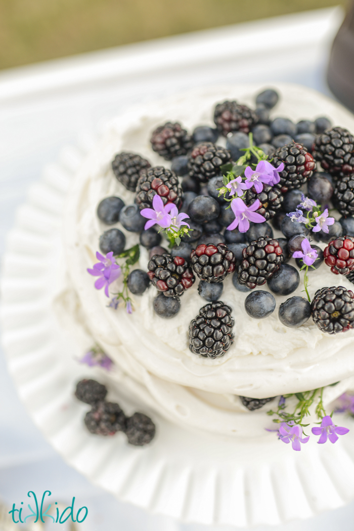 Large meringue pavlova topped with blackberries, blueberries, and fresh edible purple flowers, on a white cake stand.