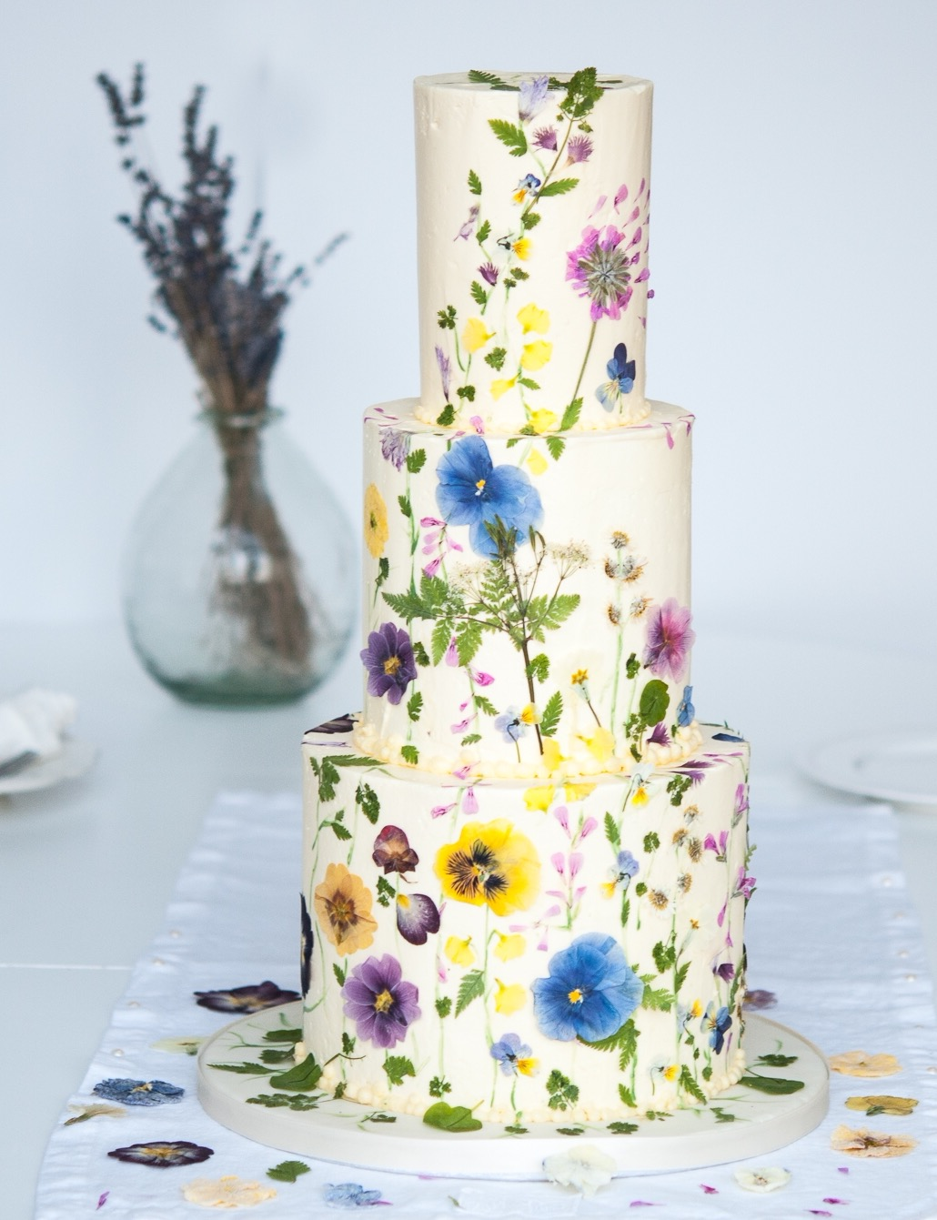 Three tier white wedding cake decorated with many colorful pressed flat fresh edible flowers.