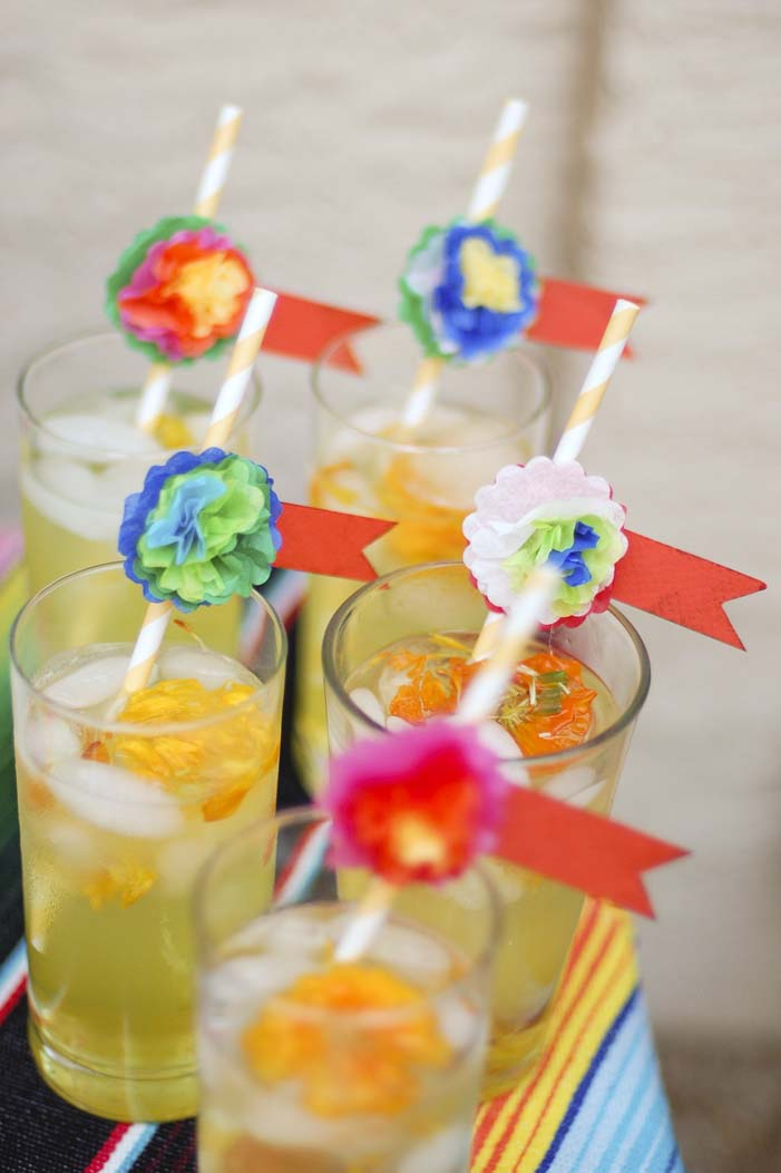 Five glasses with a pale yellow cocktail and fresh marigold flowers and ice, topped with paper straws decorated by miniature tissue paper Mexican style flowers.