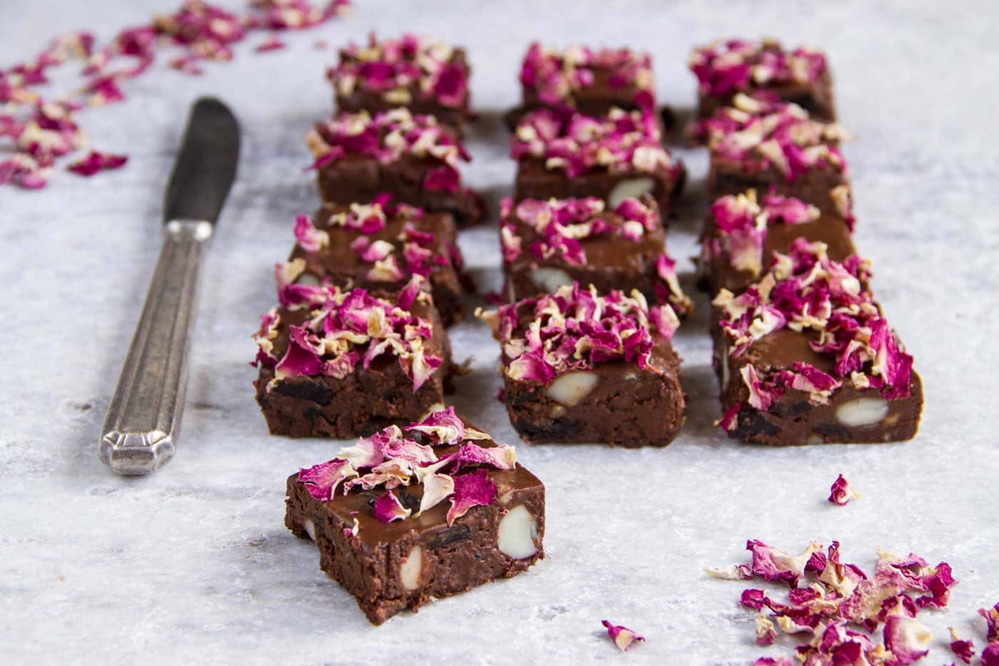 Raw rocky road chocolate candies topped with rose petals on a white surface.