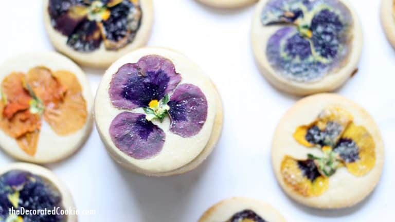 Sugar cookies decorated with real flowers on a white background.